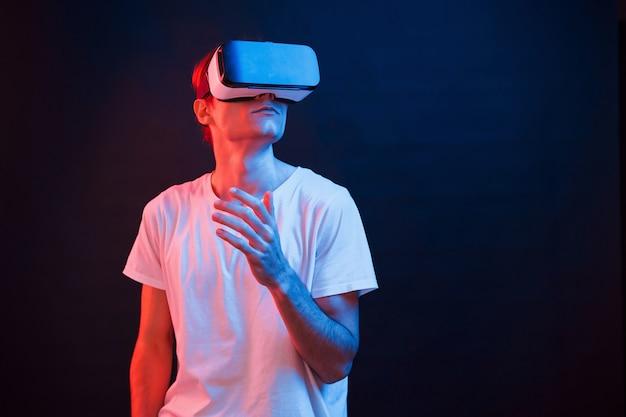 Глядя вверх. молодой человек в очках виртуальной реальности в темной комнате с неоновым освещением.