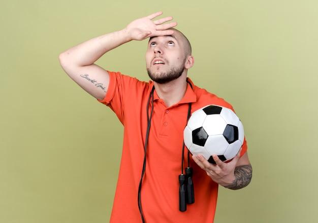 Guardando il giovane uomo sportivo con la corda per saltare sulla spalla tenendo la palla e mettendo la mano sulla fronte
