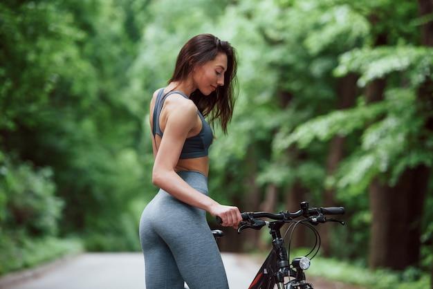Guardando il veicolo. ciclista femminile in piedi con la bici su strada asfaltata nella foresta durante il giorno