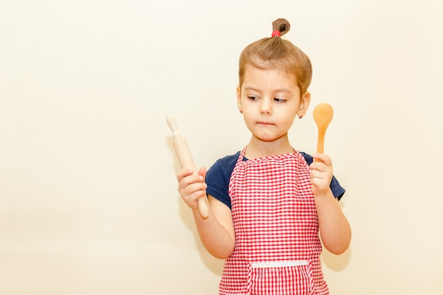 Looking with interest little girl with chef apron holding wooden rolling pin and a spoon on beige background