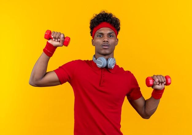 Молодой афро-американский спортивный мужчина в головной повязке и браслете с наушниками на шее, тренирующийся с гантелями