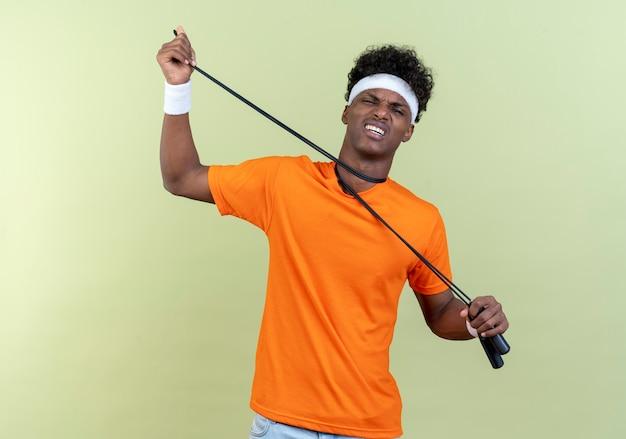 Guardando il giovane uomo sportivo afroamericano che indossa la fascia e il braccialetto che gesticolano il suicidio soffocandosi con la corda per saltare