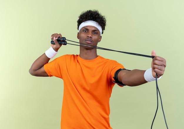 Guardando il giovane uomo sportivo afroamericano che indossa la fascia e il braccialetto che tengono la corda per saltare