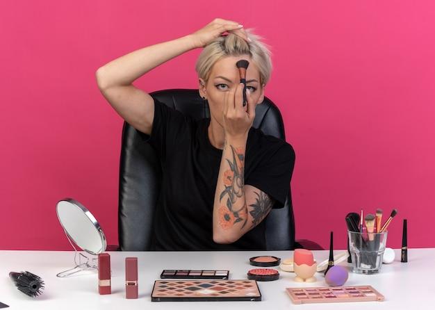 Молодая красивая девушка сидит за столом с инструментами для макияжа, нанося румяна с пудровой кистью на лоб, изолированном на розовой стене