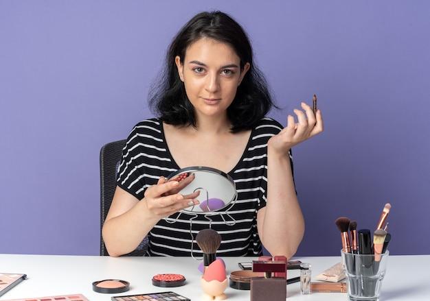 아름 다운 소녀를 찾고 파란색 벽에 고립 된 아이 라이너와 거울을 들고 메이크업 도구와 테이블에 앉아