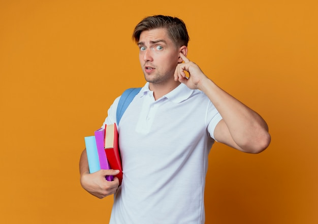 Looking young handsome male student wearing back bag holding books and closed ear with finger