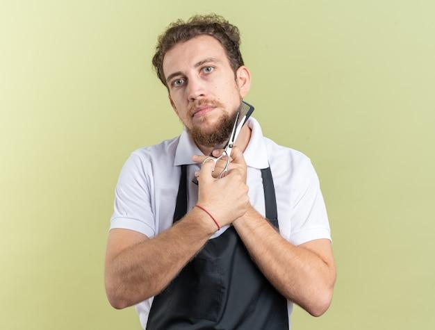 Guardando il giovane barbiere maschio che indossa l'uniforme tenendo il pettine con le forbici intorno al viso isolato sulla parete verde oliva