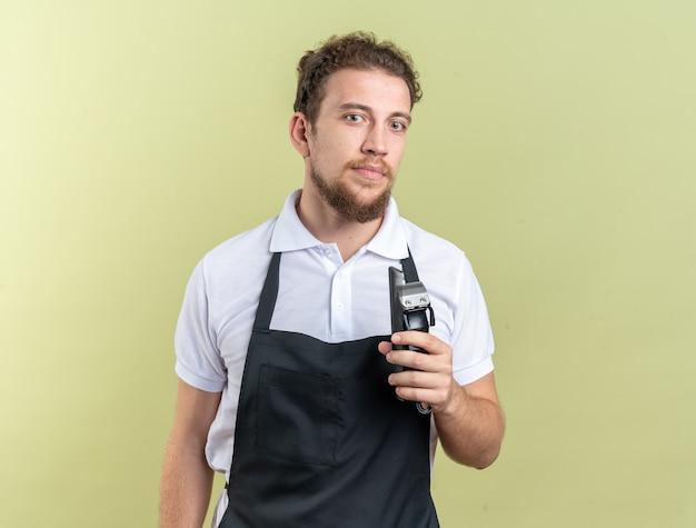 Guardando il giovane barbiere maschio che indossa l'uniforme che tiene le tosatrici con pettine isolato su parete verde oliva