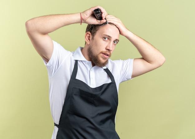 Guardando il giovane barbiere maschio che indossa l'uniforme che taglia i capelli con le forbicine isolate sulla parete verde oliva