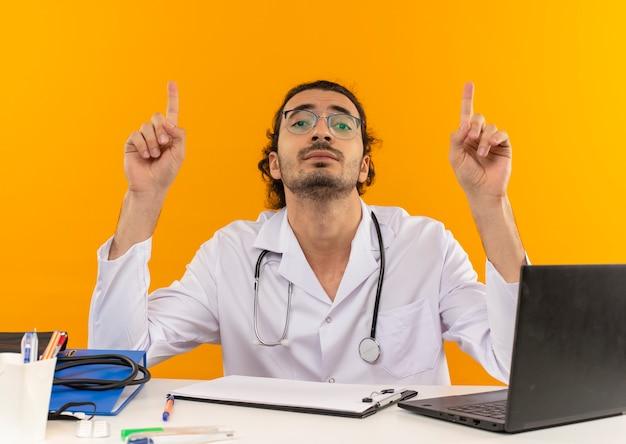 Guardando un giovane medico maschio con occhiali medici che indossa un abito medico con stetoscopio seduto alla scrivania