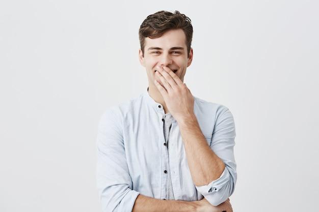 ハンサムなスタイリッシュな若い白人男性モデルは、黒い髪と青い目のlooknigと水色のシャツに身を包んだ、手のひらの後ろに笑顔を隠し、腕を組んで立って、幸せで満足しています。
