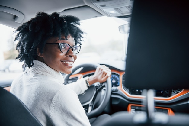 Looks back. young african american woman sits inside of new modern car.