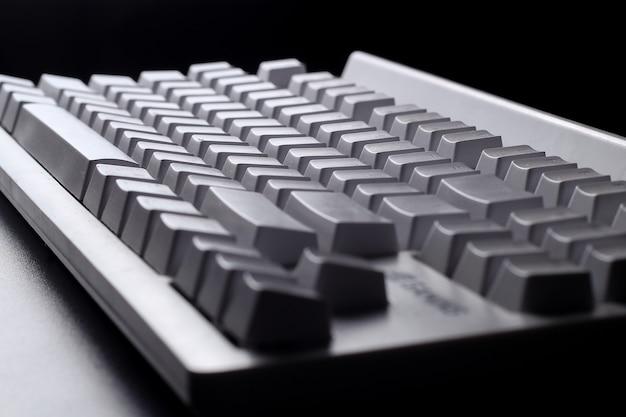 Присматривается белая клавиатура на черном фоне с небольшим освещением простая концепция