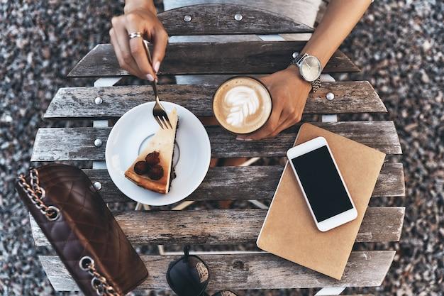 Выглядит вкусно. крупным планом вид сверху молодой женщины, держащей чашку кофе, сидя в ресторане на открытом воздухе