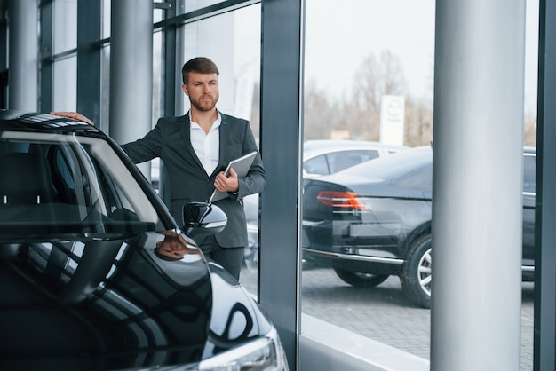 Guarda lontano. uomo d'affari barbuto elegante moderno nel salone dell'automobile