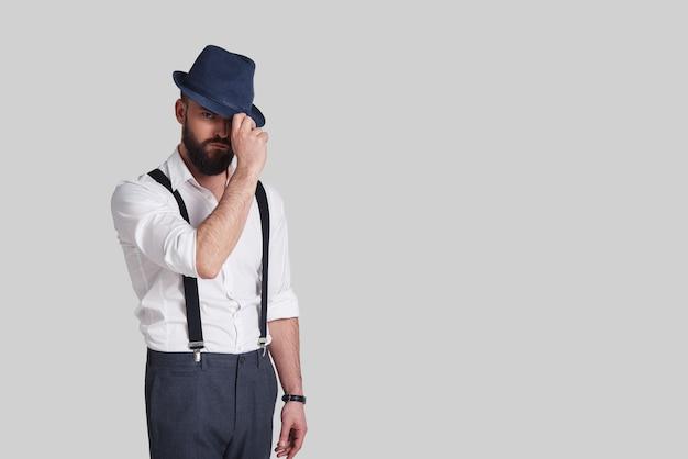 Похоже на гангстера. красивый молодой человек в подтяжках поправляет шляпу и смотрит в камеру, стоя на сером фоне