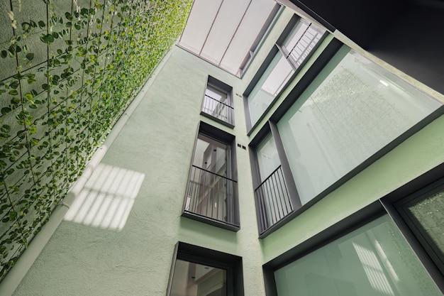 バルセロナの黒いフレームの窓に垂直ガーデニングを備えたモダンな住宅のルックアップビュー...