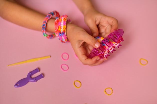 輪ゴムでおもちゃのブレスレットを織る織機は、子供が手に持っています