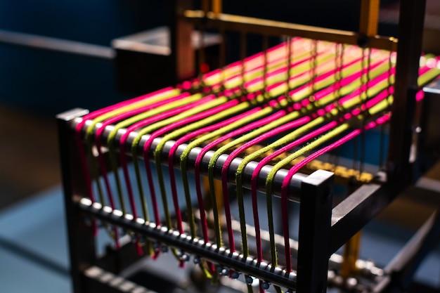 Ткацкие станки, аксессуары, тканые шарфы, цветные нити крупным планом.