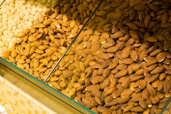Loose almonds on the store shelves. A mixture of nuts.