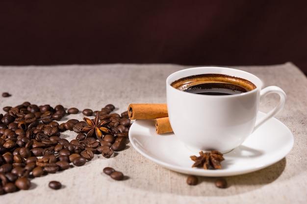 明るい色の帆布で覆われたテーブルのマグカップとスターアニスの横にある緩いコーヒー豆
