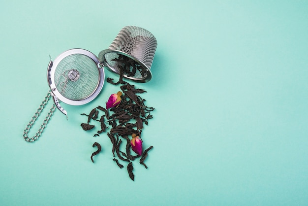 Loose dried tea herbs spilled from the tea strainer against colored backdrop
