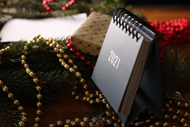 Перекидной календарь стоит на деревянном столе среди веток елки и украшений