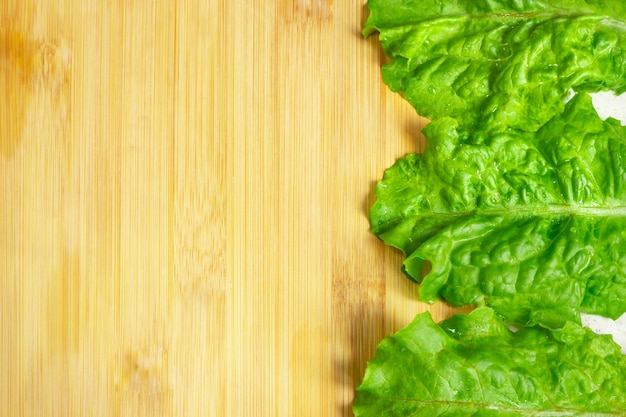 Loose leaf lettuce close up top view  green lettuce leaves on wooden table natural green  frame