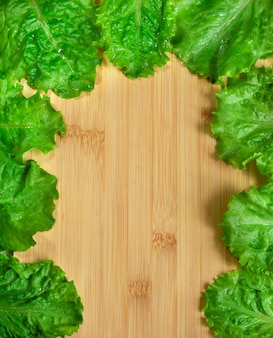 Loose leaf lettuce close up top view  green lettuce leaves on wooden table