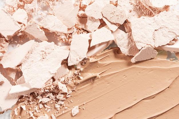 Рассыпчатая светлая пудра и мазок крупным планом тонального крема. понятие о декоративной косметике, макияже. рекламная макросъемка.