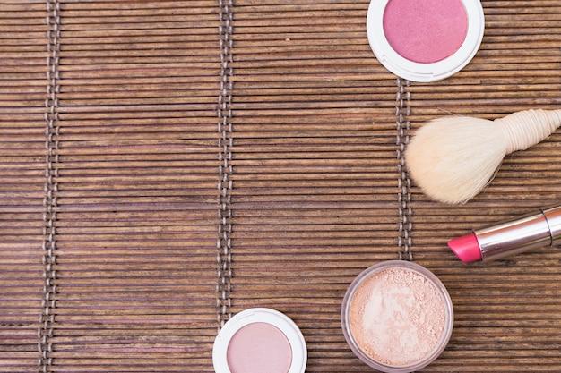 Loose powder; pink lipstick; blusher and makeup brush on placemat