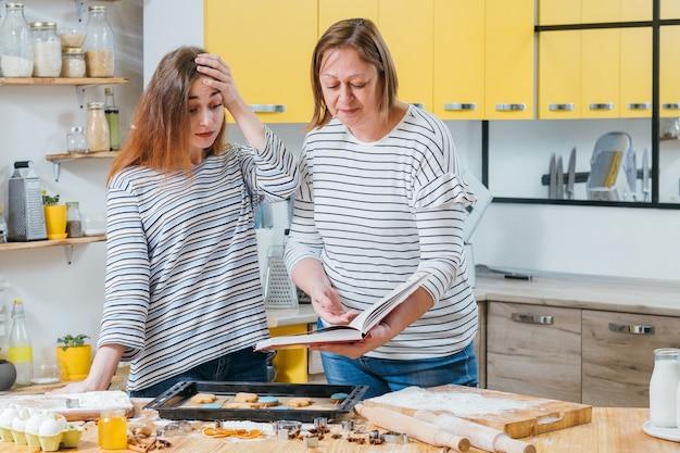 루저 셰프. 어머니는 요리 책을 들고, 비스킷을 요리하는 딸의 실수를 지적했습니다.
