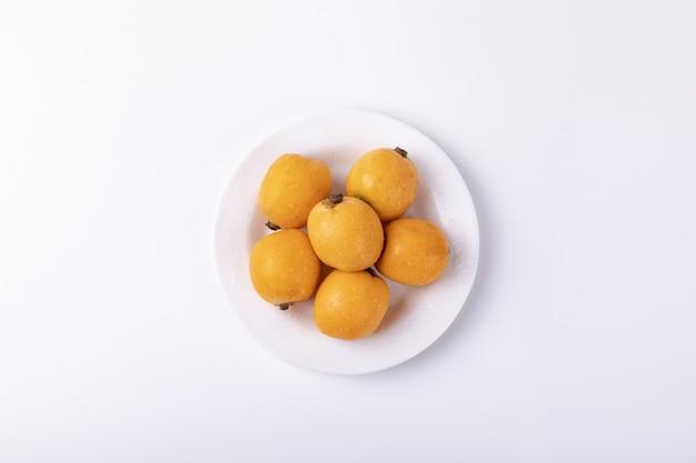흰색 테이블에 고립 된 비파 과일