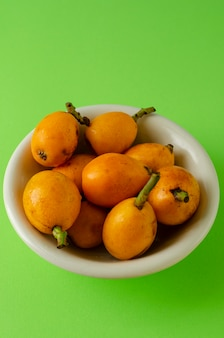 Loquat fruits in a white bowl on bright green