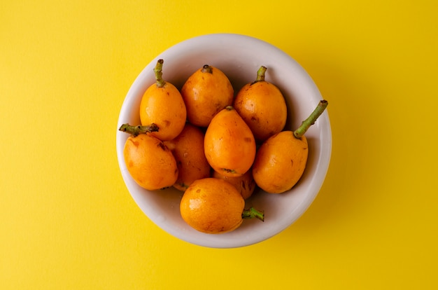 Loquat fruits in a white bowl on bright yellow