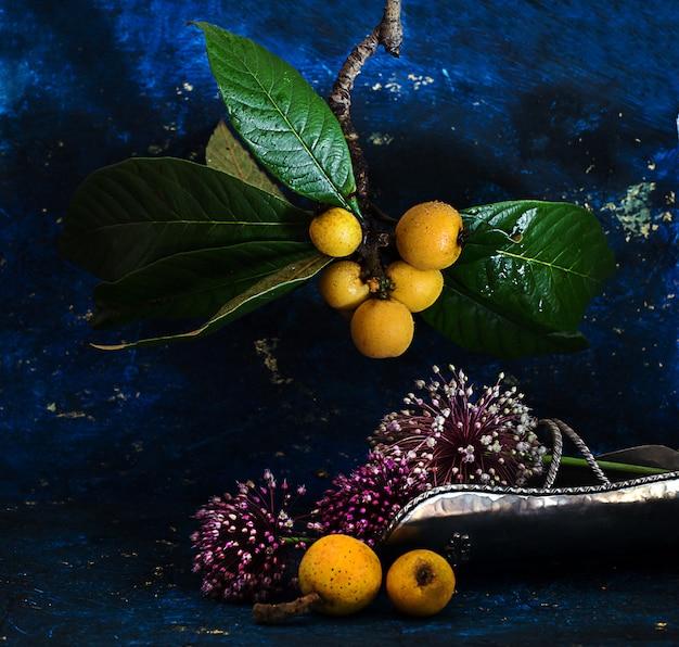 Loquats and allium flowers over blue dark