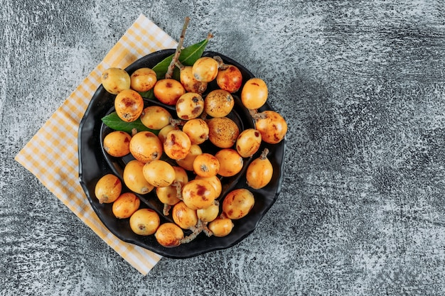 Loquats in a bowl on a cloth and gray textured background. top view. space for text