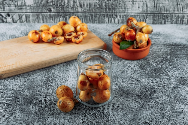 Loquats in a jar, bowl and cutting board on a gray textured background. high angle view.