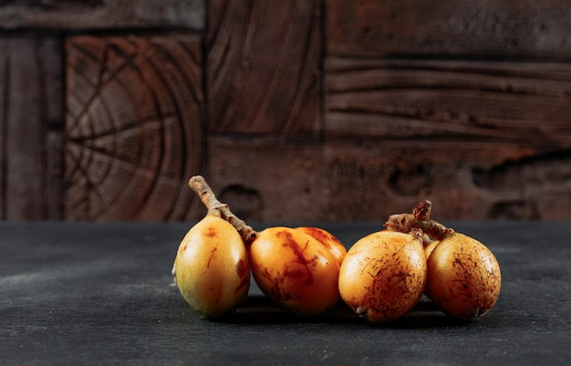 Loquats side view on a dark textured and wooden background space for text