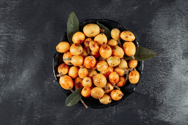 Loquats with leaves in a bowl on dark textured background, top view.