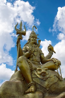 Lord shiva with blue sky in wat chom tham at mea on in chiang mai, thailand