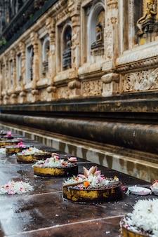 インド、ビハール州のブッダガヤで雨が降っている間、マハーボディ寺院で咲く蓮と花でこれらのプラットフォームの上を歩く仏lord