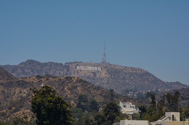 Лос-анджелес, калифорния знак голливуда с видом на лос-анджелес. знаковый знак изначально был создан в 1923 году.