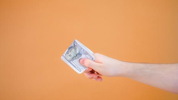 Ð¡lose-up hand gives a bundle of dolars on orange background
