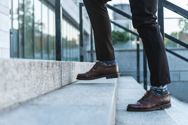 Ð¡lose-up of male legs in business trousers and shoes walking up the stairs
