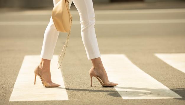 Закройте ноги женщины, ходить по пешеходному переходу. женщина носит туфли на высоких каблуках. сумочка в руке женщины.