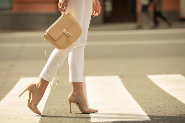 С横断歩道の上を歩く女性の足を失う。女性はハイヒールで靴を履いています。女性の手にハンドバッグ。