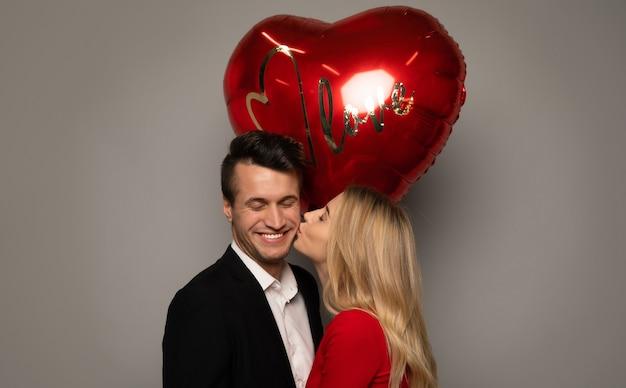 Фото крупным планом очаровательной дамы, которая целует своего красивого парня в щеку, одновременно даря ему большой красный воздушный шарик в форме сердца.