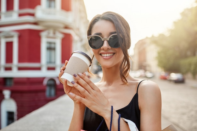 サングラスで黒髪の美しい白人少女の肖像画を失い、黒のドレスで歯を浮かべて、コーヒーを飲みながら、ショッピングモールでの長い買い物の後にリラックスします。