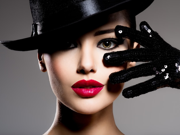 Сlose-up portrait of a woman in a black hat and gloves with red lips posing